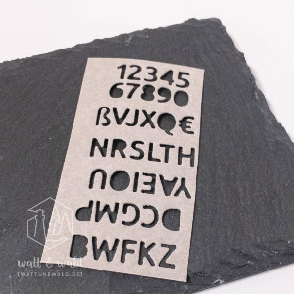 Buchstaben gestanzt aus grauem Waschpapier
